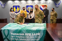 Col. Katrina Stephens, installation commander, signs a Sexual Assault Awareness and Prevention Month proclamation at Hanscom Air Force Base, Mass., March 30, while Staff Sgt. Samantha Marchionda, from left, Rachel Desharnais, Jersouk Touy, Chief Master Sgt. William Hebb, installation command chief,  Staff Sgt. David Ahn and Master Sgt. Jessica Subia, members of the Sexual Assault Prevention Response Office, look on. April is Sexual Assault Awareness and Prevention Month.  (U.S. Air Force photo by Mark Herlihy)
