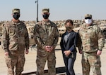 Three masked male military officers stand with a female masked civilian at Camp Arifjan, Kuwait.