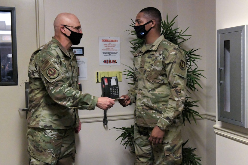 Photo shows the two exchanging a coin in an entryway.