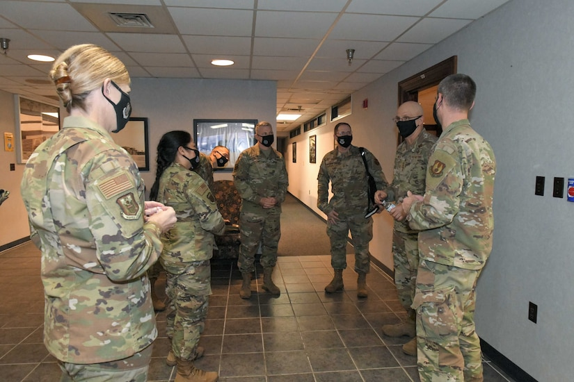Photo shows a group of people standing in a hallway talking.