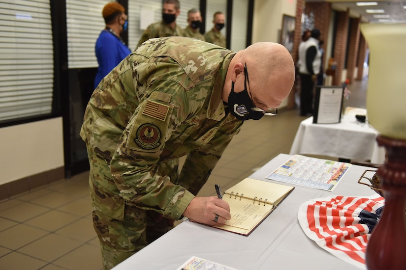 Photo shows the general signing a book on a table.