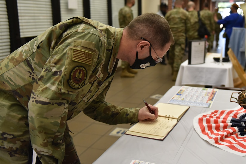 Photo shows the chief signing a book on a table.
