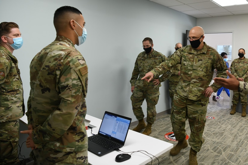Photo shows command team speaking to two Airman standing behind computers.