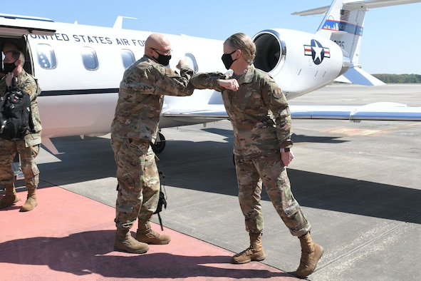 Photo shows the generals elbow bumping on the flight line.