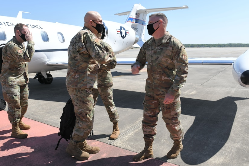 Photo shows two meet going to elbow bump on the flight line.