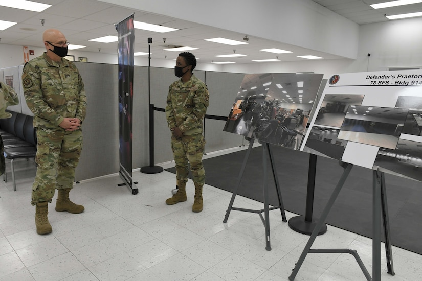 Photo shows the general looking at two informational boards while an Airman speaks to him.