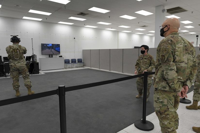 Photo shows the general watching an individual using a VR device on his head.