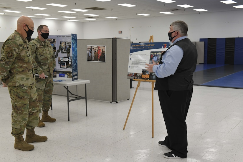 Photo shows three men looking at a poster board on an easel.