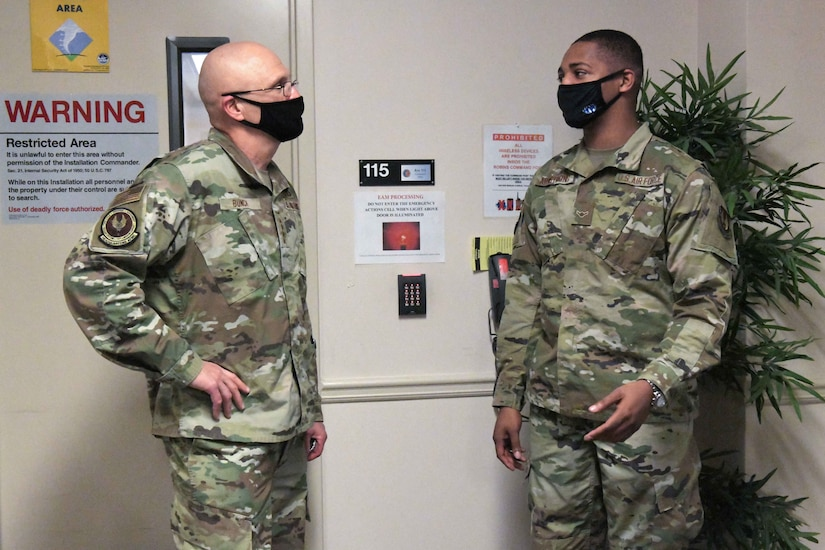 Photo shows two men standing in an entryway speaking to one another.