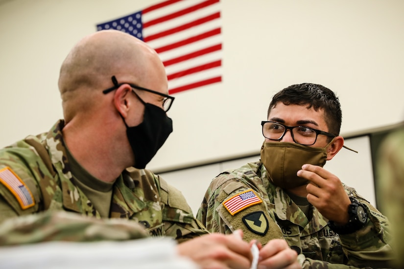 """U.S. Army Reserve Spc. Daniel Bush, left, civil affairs specialist with the 353rd Civil Affairs Command, and Staff Sgt. Marco Campos, right, a civil affairs specialist with the 410th Civil Affairs Battalion, greet each other during the inprocessing portion of the 2021 U.S. Army Civil Affairs and Psychological Operations Command (Airborne) Best Warrior Competition at Fort Jackson, S.C. on April 6. Soldiers from across the nation traveled to compete in the 2021 U.S. Army Civil Affairs and Psychological Operations Command (Airborne) Best Warrior Competition, hosted from April 5-10, at Fort Jackson, S.C. The USACAPOC(A) BWC is an annual competition that brings in the best Soldiers across USACAPOC(A) to earn the title of """"Best Warrior"""" among their peers after being evaluated on their individual ability to adapt and overcome challenging scenarios and battle-focused events, testing their technical and tactical abilities under stress and extreme fatigue."""