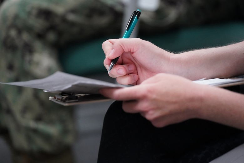 A close up photo of a military dependents hands as they fill out a medical questionnaire in a medical waiting room.
