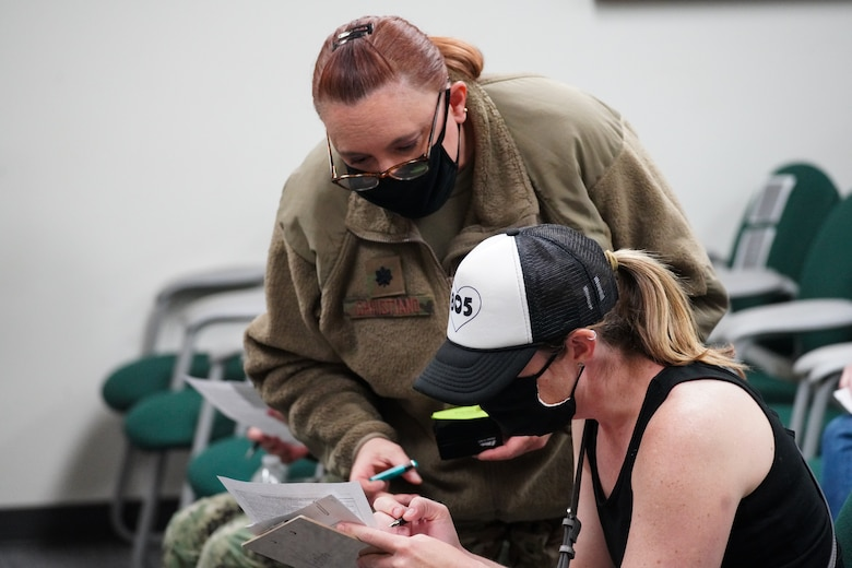 A U.S. Air National Guard member looks over the shoulder of a military dependent who is sitting down filling out a medical questionnaire