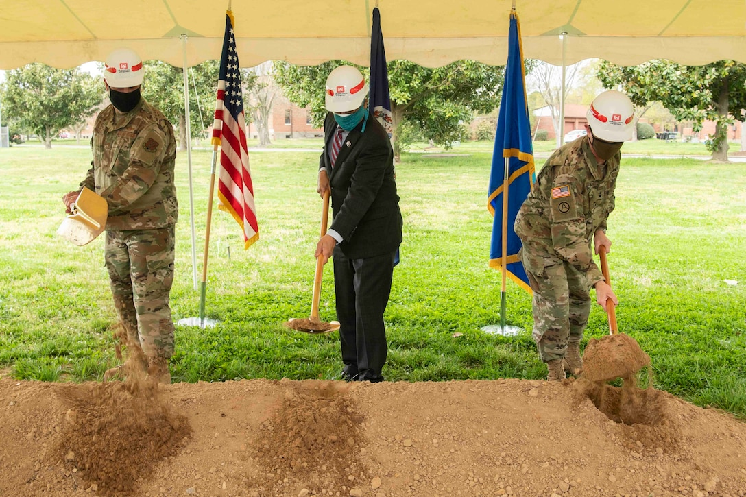 Three men wearing hard hats ceremoniously turn dirt during a ground breaking ceremony