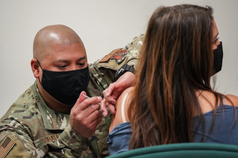 A U.S. Air National Guard member gives a COVID-19 vaccination into the arm of a military dependent.