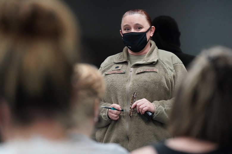 A U.S. Air National Guard member standing in front of a group of military dependents inside a medical waiting room while answering questions about the COVID-19  vaccine.