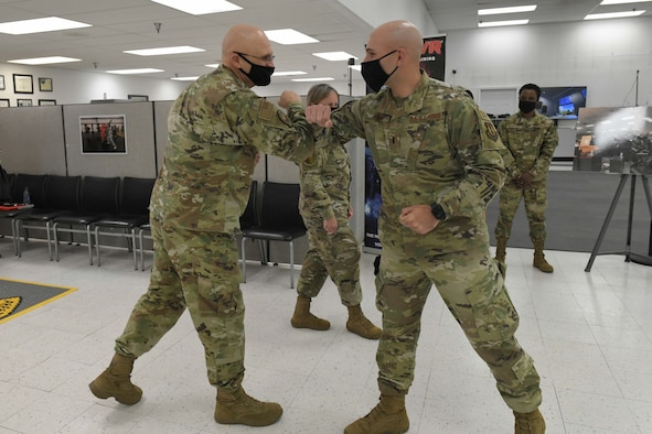 Photo shows the general and the Airman elbow bumping.
