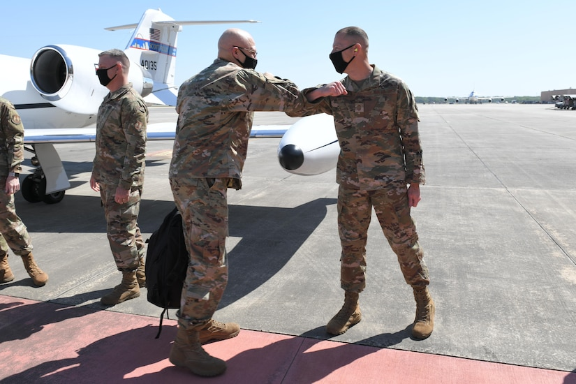 Photo shows the general bumping elbows with the chief on the flight line.