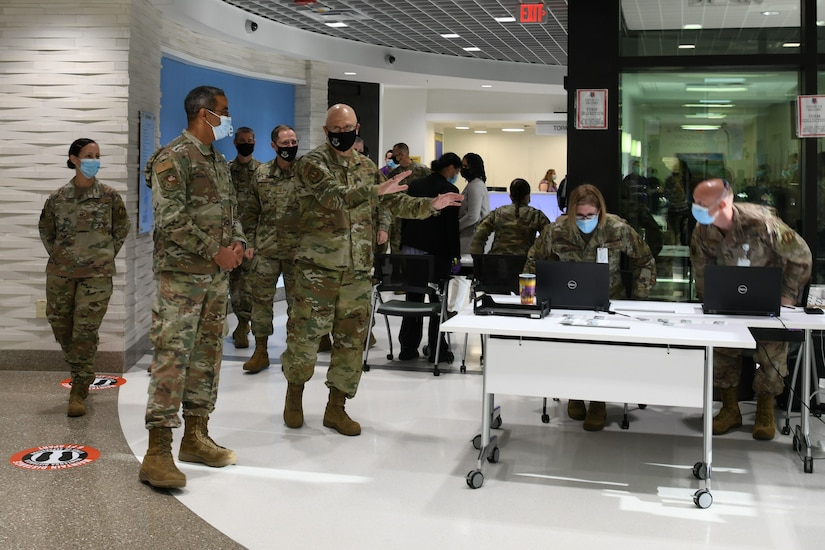 Photo shows the command team being led by tables manned by personnel near an entrance to the hospital.