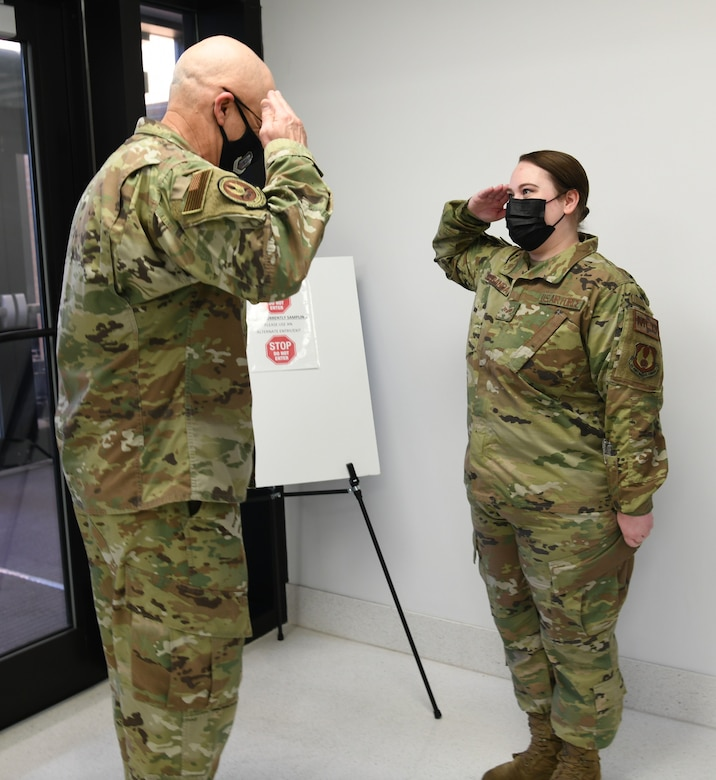 Photo shows the general and Airman saluting each other.