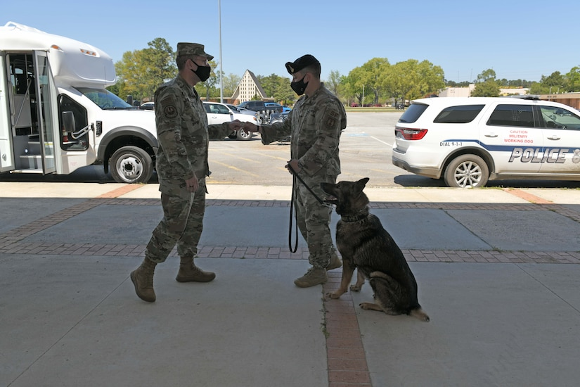 Photo shows Chief handing his coin to an Airman while his Military Working Dog sits at his feet.