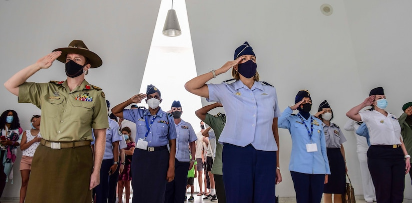 Women from varied multinational militaries salute.