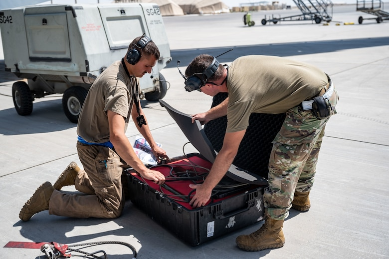 Airman 1st Class Brandon Weber and Staff Sgt. Daniel Destefano pack up equipment.