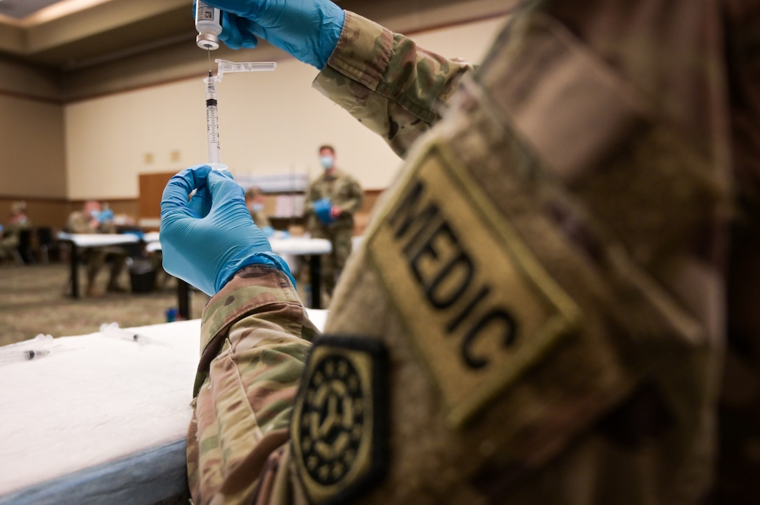 U.S. Army combat medic draws the COVID-19 vaccine into a syringe in the Tinley Park Convention Center in Tinley Park, Illinois, February 26, 2021. Medical professionals draw the vaccine as a part of the daily process to match the numbers of vaccines prepared with the number of patients receiving it. (U.S. National Guard photo by Staff Sgt. Aaron Rodriguez)