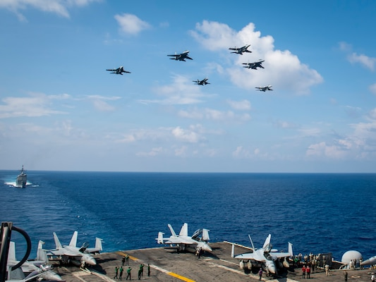 Aircraft from Carrier Air Wing (CVW) 11 and the Royal Malaysian Air Force (RMAF) fly above the aircraft carrier USS Theodore Roosevelt (CVN 71).