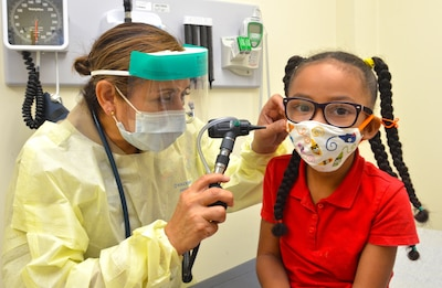 A pediatric nurse practitioner checks a 5-year-old child's ears.
