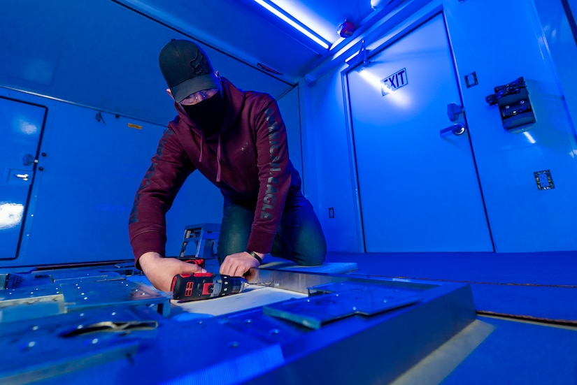 Photo of Sheet Metal Mechanic Thomas Hodorovich installs hardware in a BDOC shelter.