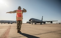 Airman uses hand signals to guide airplane.