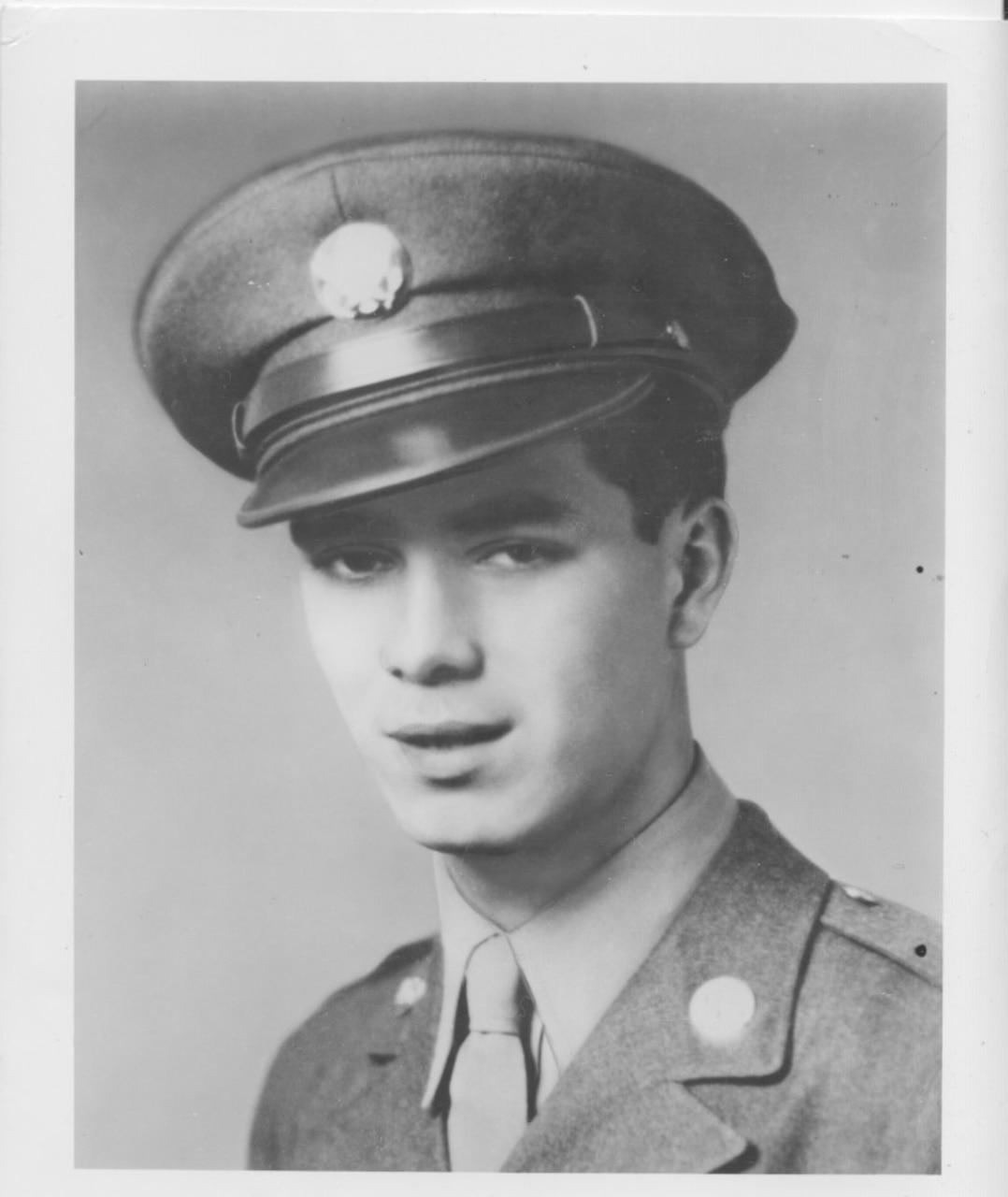 A young man wears a cap and dress uniform.