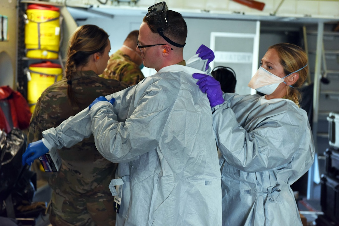 A female airman wearing personal protective equipment helps another airman put on a medical gown.