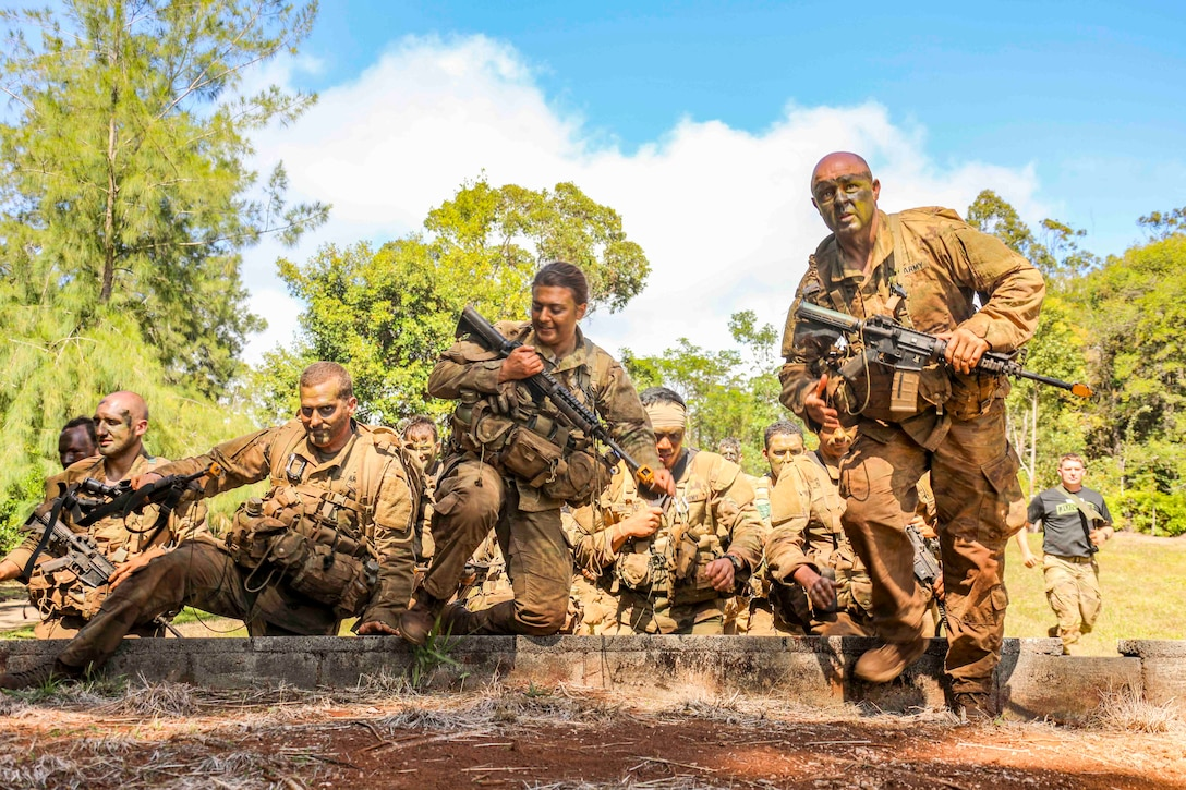 A group of soldiers move together while holding weapons.