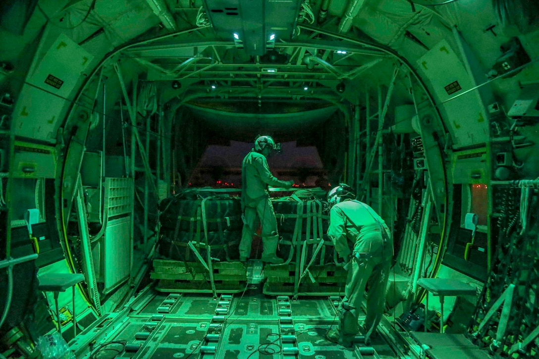 Two Marines illuminated by green light work inside an aircraft.