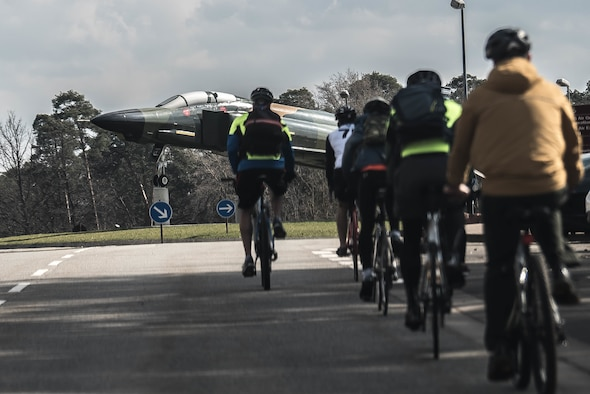 Several people ride their bicycles toward an aircraft static display.