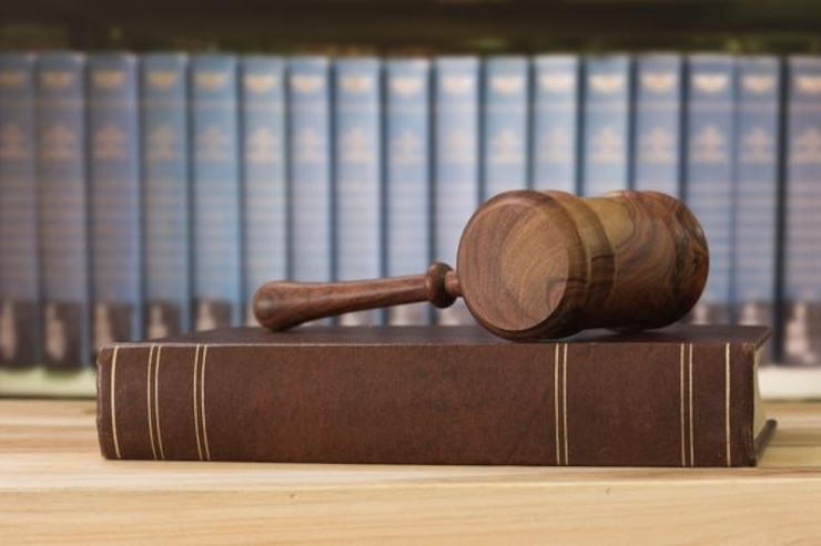 A judges gavel rests on a plain brown book