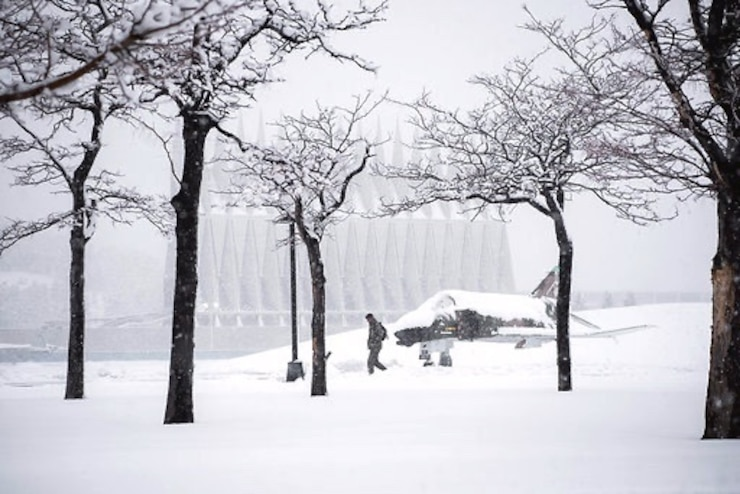 A cadet walks to classes through the snow.