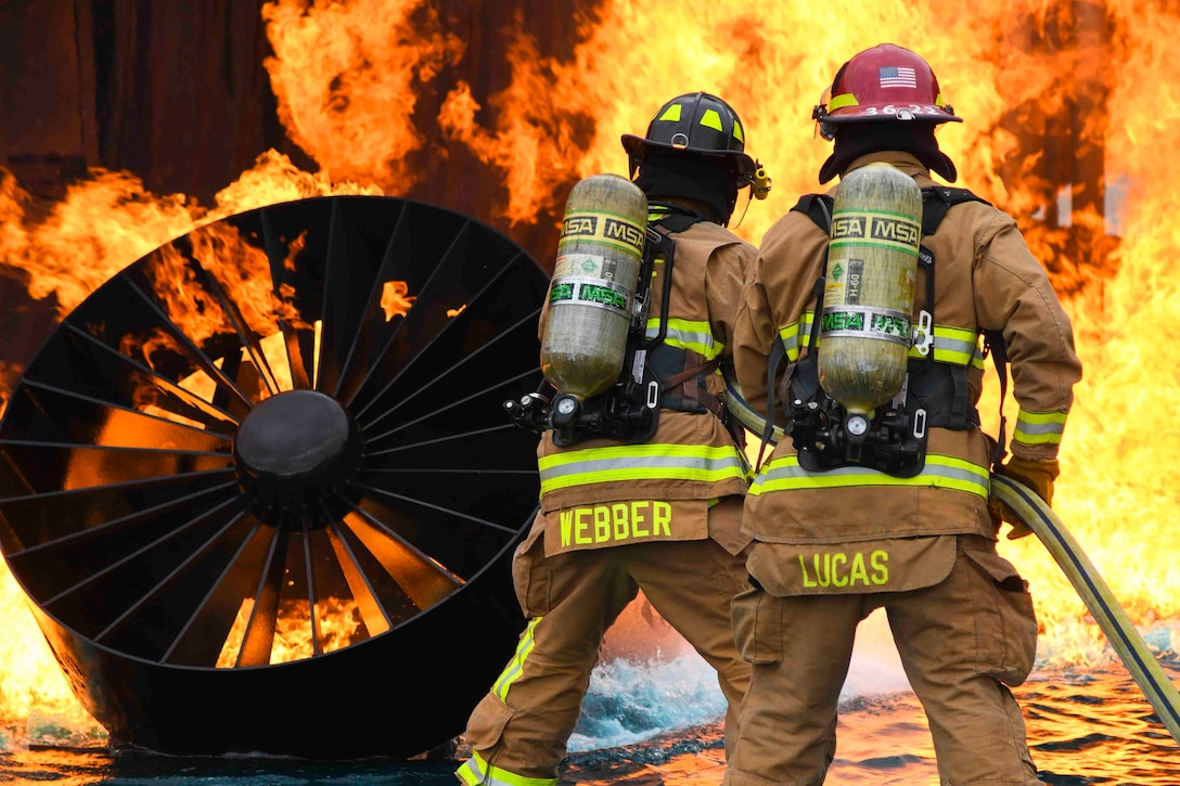 Two Air Force firefighters use a water hose to put out a fire.