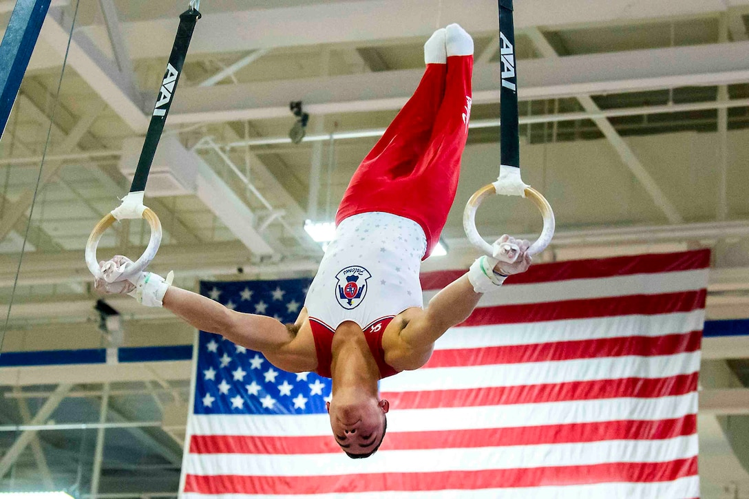 A gymnast holds onto rings while lifting himself up in the air.