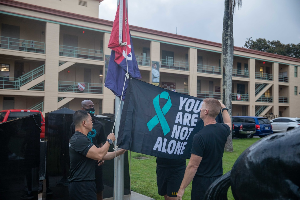 Two men place a flag on a flagpole. Another man watches.