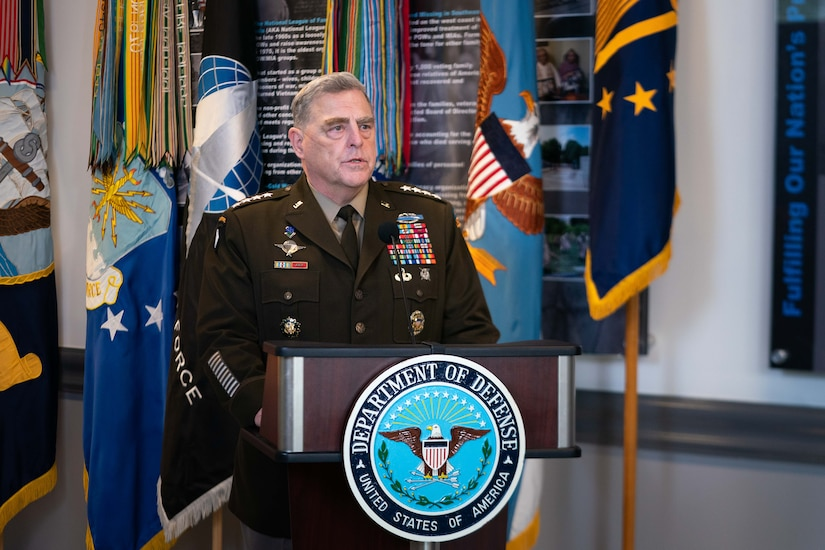 A general officer, standing at a lectern with flags behind him, speaks.