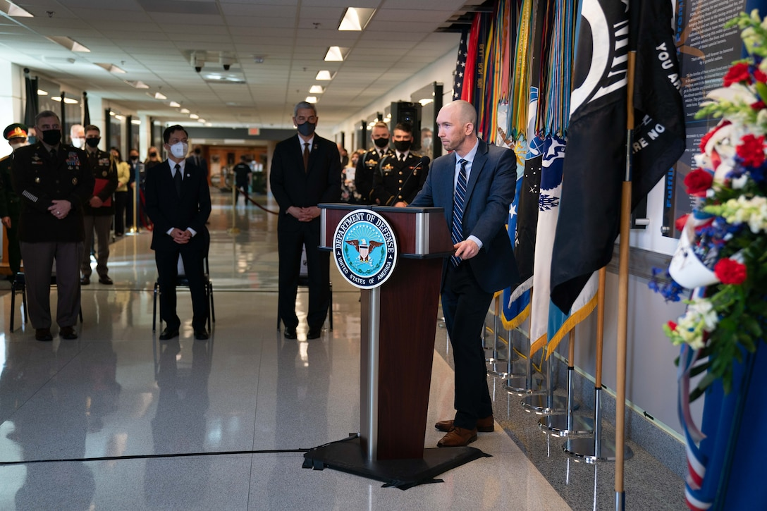 A civilian stands at a lectern with flags behind him and speaks to a group at a commemoration ceremony.