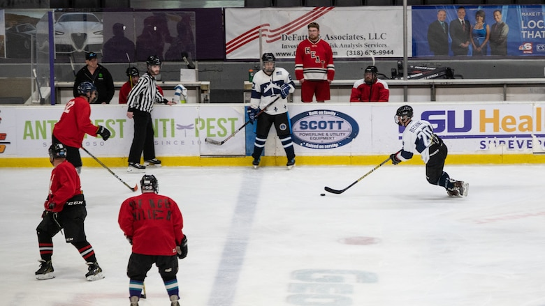 An Airman from the Barksdale Bombers hockey team from Barksdale Air Force Base, Louisiana, prepares to maneuver through opposing players during the Mudbugs Adult Hockey League championship game at Hirsch Memorial Coliseum, Shreveport, Louisiana, March 31, 2021.