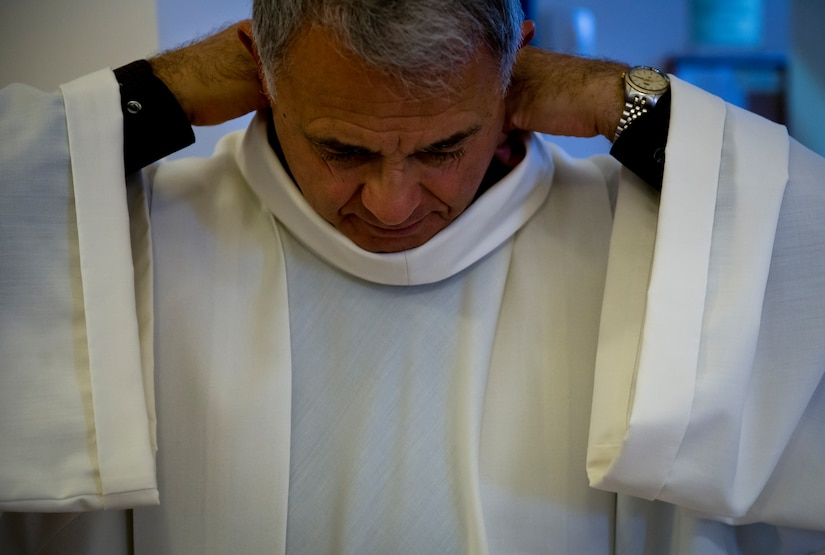 Retired Chaplain (Lt. Col.) Robert Bruno adjusts his white alb before entering the dormitory chapel for morning prayer. The alb is the common vestment for all ministers at Mass.  (U.S. Air Force photo/Staff Sgt. Andrew Lee)