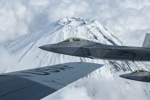 U.S. Air Force Raptors from the 199th Fighter Squadron fly alongside a U.S. Air Force KC-135 Stratotanker from the 909th Air Refueling Squadron during 5th generation fighter training near Mt. Fuji, Japan, April 1, 2021. The F-22 Raptors are currently operating out of Marine Corps Air Station Iwakuni, Japan, to support U.S. Indo-Pacific Command's dynamic force employment concept. (U.S. Air Force photo by Senior Airman Rebeckah Medeiros)
