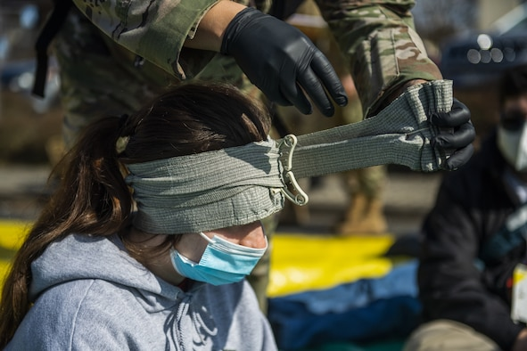 A volunteer for the 52nd Fighter Wing Medical Group exercise Ready EAGLE receives simulated medical attention at Spangdahlem Air Base, Germany, March 26, 2021. The training event at the MDG lasted the entire week and culminated in a capstone event, which simulated a disaster at the base theater. (U.S. Air Force photo by Senior Airman Ali Stewart)