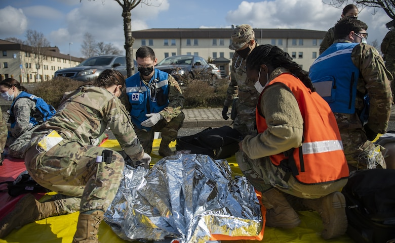 A volunteer for the 52nd Medical Group exercise Ready EAGLE lies on a tarp while receiving simulated medical attention by MDG Airmen at Spangdahlem Air Base, Germany, March 26, 2021. During the simulated disaster response exercise, Wing Inspection Team members assessed the performance of Airmen and read off scenario cards to better help the team understand patient injuries. (U.S. Air Force photo by Senior Airman Ali Stewart)