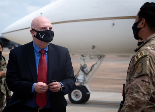 Honorable John P. Roth, acting Secretary of the Air Force, recieves a patch from Staff Sgt. Keola Miller, 2nd Security Force Squadron military working dog handler, during a tour at Barksdale Air Force Base, Louisiana, April 6, 2021.