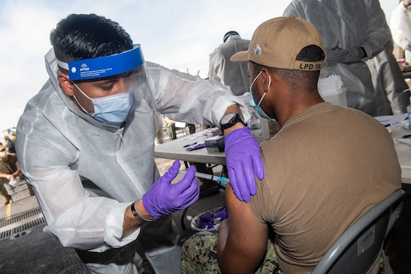 OKINAWA, Japan (Feb. 14, 2021) Hospital Corpsman 1st Class Javier Flores shoots a COVID-19 vaccination into the arm of Retail Specialist Seaman Jordan Davis aboard amphibious transport dock ship USS New Orleans (LPD 18). New Orleans, part of the America Expeditionary Strike Group, along with the 31st Marine Expeditionary Unit, is operating in the U.S. 7th Fleet area of responsibility to enhance interoperability with allies and partners and serve as a ready response force to defend peace and stability in the Indo-Pacific region. (U.S. Navy photo by Mass Communication Specialist 2nd Class Kelby Sanders)
